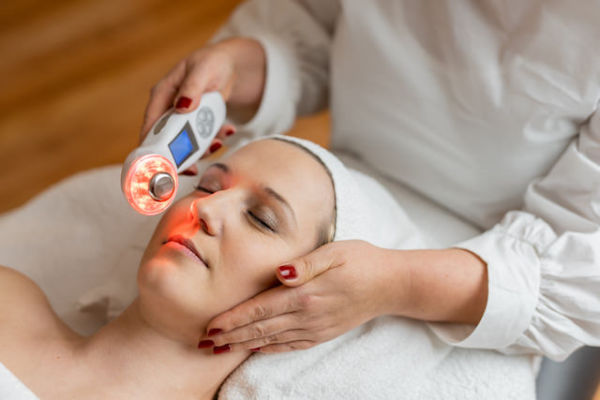 Frau während einer Gesichtbehandlung mit Ultraschall